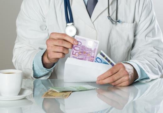Egy orvos az asztalánál egy borítékból pénzt vesz ki.