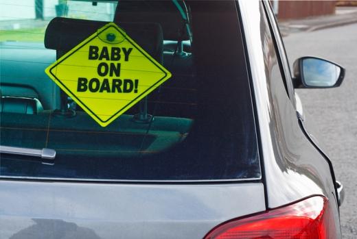 Egy autó hátsó szélvédőjén, sárga, baby on board felírat.