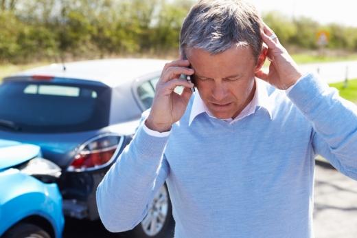 Egy férfi telefonál, mögött két autó összeütközve.