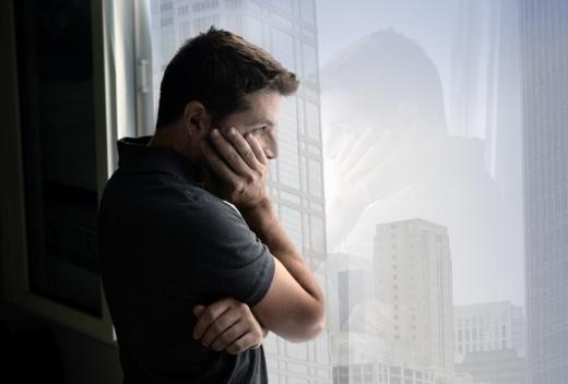 Egy férfi állát támasztva, egy felhőkarcoló ablakán bámulva gondolkozik.