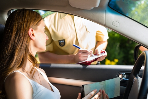 Egy nő ül az autóban, miközben egy rendőr éppen megbírságolja.
