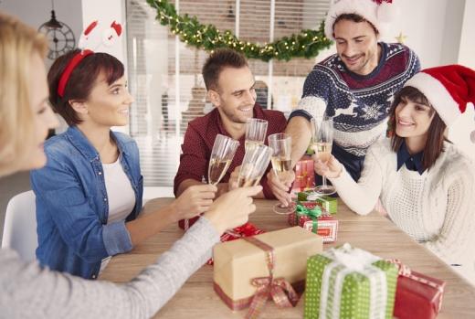 Emberek egy asztalnál karácsonyi sapkába és pulóverben, pezsgővel koccintanak az ajándékok között.