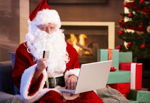 A mikulás, karácsonyfa és ajándékok előtt, laptoppal a kezében bankkártyát tart a kezében.