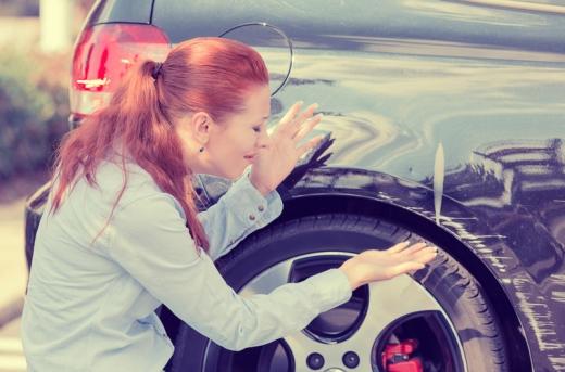 Egy nő elkeseredve nézi autója jobb hátsó részét karambol után.