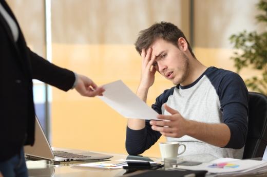 Egy kéz egy felmondási papírt ad, egy az asztalánál ülő férfinek.
