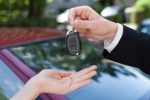 Egy autó szélvédője előtt egy férfi kéz egy slusszkulcsot ad egy nő kezében.