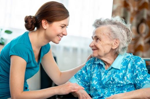 Egy fiatal nő mosolyogva ránéz egy idős nőre.