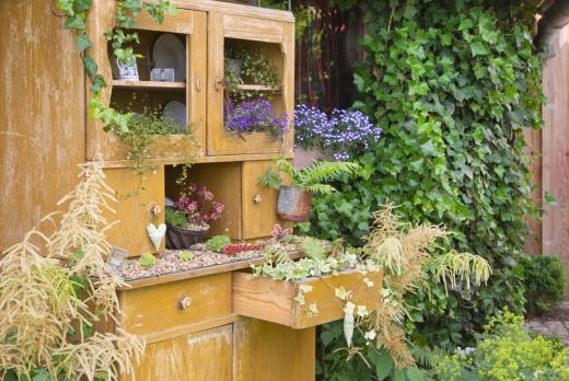 A kertben egy fiókos, ajtós szekrény, amiben virágok vannak ültetve.