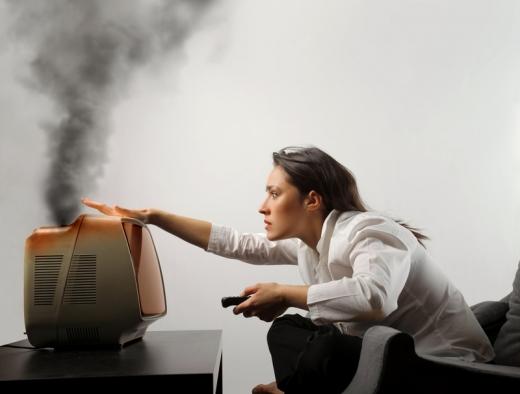 Egy nő a foteljében előrehajolva rácsap egy régi kis tévére, ami füstöl.