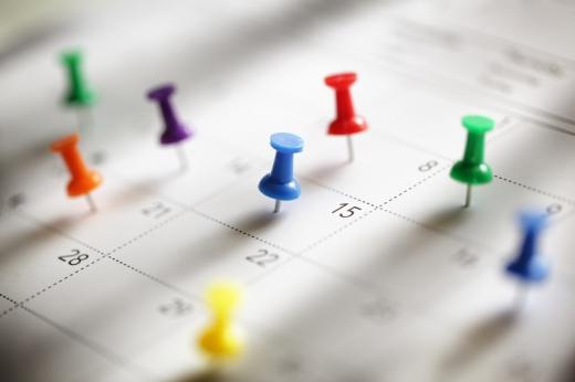 Egy naptár tele van tűzdelve színes gombostűvel.