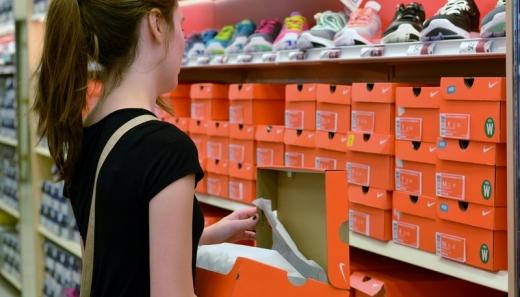 Egy lány egy cipőboltban, a polc előtt cipős dobozt tart a kezében.