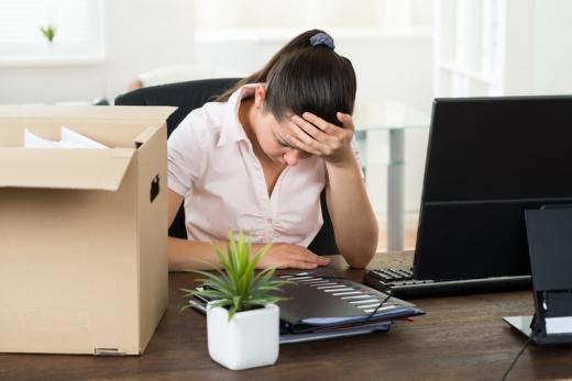 Egy nő az asztalánál fogja a fejét, mellett a számítógépe és egy dobozban a papírjai.