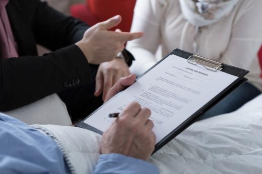 Egy fekvő beteg kezében egy nyomtatvány amit aláír.