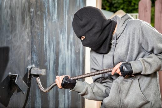 Egy fekete maszkban, egy férfi, feszítő vassal, ki akar nyitni egy fa ajtót.