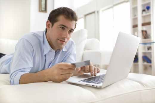 Egy férfi hason fekve laptopot használ.