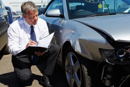 Egy kárszakértő mappával a kezében vizsgál egy törött autót.