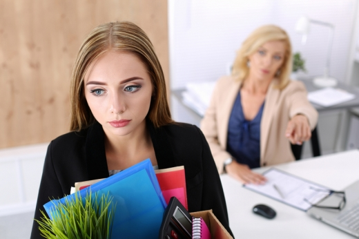 Egy nő a háttérben előre mutat egy másik nőnek aki szembe jön egy dobozzal, amibe a munkaeszközei vannak.