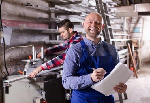 Műhelyben egyik férfi a háttérben dolgozik, a másik papírral és tollal ránk mosolyog.