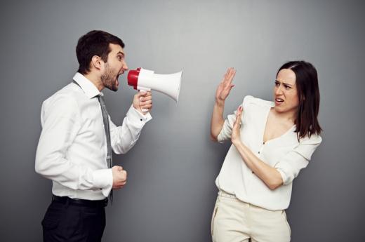 Egy férfi hangosbemondóval kiabál egy kezét maga elé tartó nőre.
