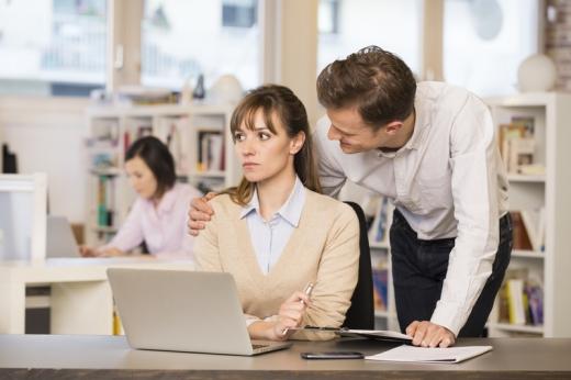 Egy nőt, aki a laptopja előtt ül és elgondolkodik egy férfi hátulról, lehajolva átölel a vállánál.
