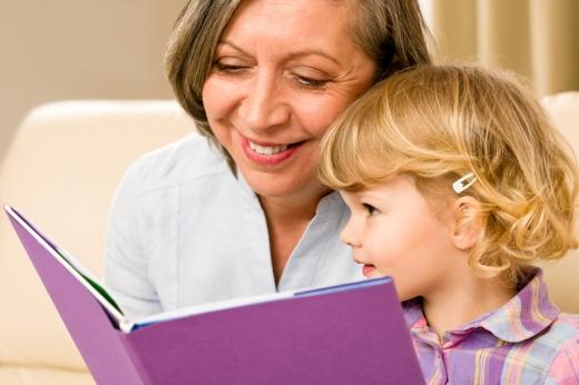 Nagymama és unokája egy lila külsejű könyvet néznek mosolyogva.