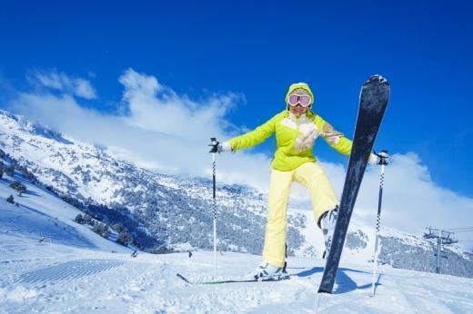 A havas dombtetőn egy nő sífelszerelésben egy sílécét felénk emeli.