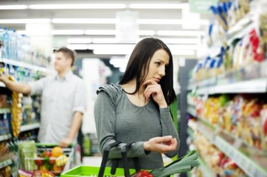 Fiatal nő kezében kosárral egy bevásárlóközpontban egy polc előtt gondolkodik mit vegyen.