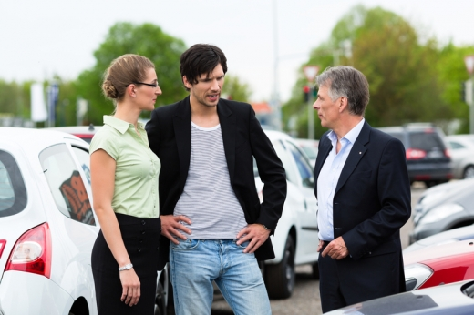 Autókereskedő egy autót mutat egy párnak a kereskedésben.
