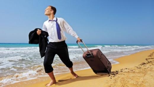 Öltönyös férfi, zakóval a kezében, zokni nélkül, húz egy kerekes bőröndöt a tengerparton a homokban.