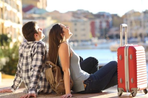 Fiatal pár kikötőben ülve, hátratámaszkodva élvezik a pihenést.
