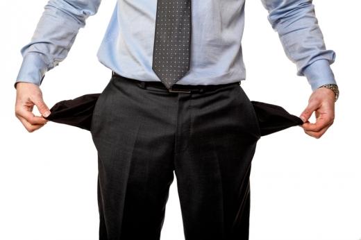 Egy férfi két kezével széthúzza üres zsebeit.