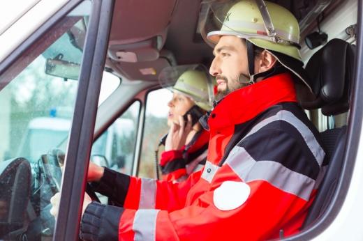 A tűzoltóautó fülkéjében egyik férfi vezet a másik telefonál.