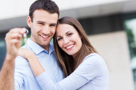 Fiatal pár összeölelkezve áll és a férfi kezében egy kulcs.