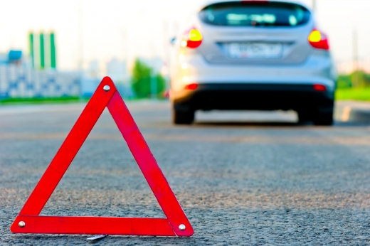 Egy elakadásjelző háromszög van az aszfalton, mögött homályosan egy autó látható.