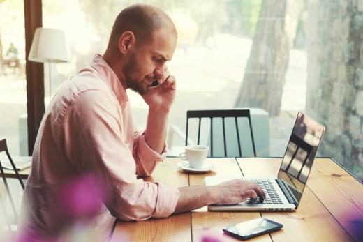 Egy férfi asztalnál ül, egyik kezében laptopot gépel, másikkal telefonál.