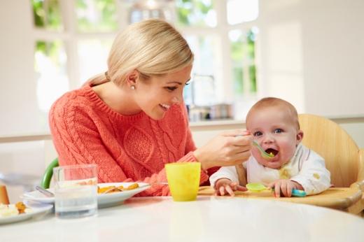 Szőke anyuka eteti etetőszékben járó kisbabáját.