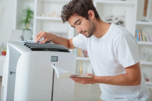 Egy férfi egy gépre támaszkodva, annak használati utasítását olvassa.