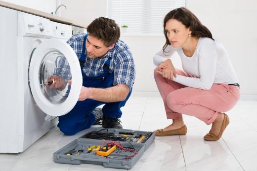 Egy férfi mosógépet szerel, mellette a tulajdonos nő figyeli.