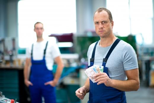 Egy műhelyben két kantáros nadrágos férfi közül az egyik papírpénzt mutat felénk.