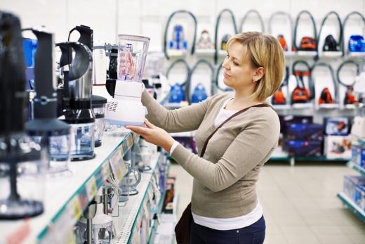 Egy nő leemel egy turmixgépet a polcról egy elektronikai boltban.