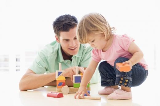 Kislány az asztalon guggolva építőkockával játszik, közben apukája nézi.