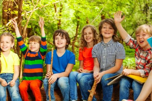 Hat kisgyerek az erdőben egy nagy farönkön ülve jelentkezik.