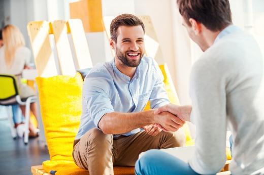 Két férfi mosolyogva, ülve megegyezés után kezet fognak.