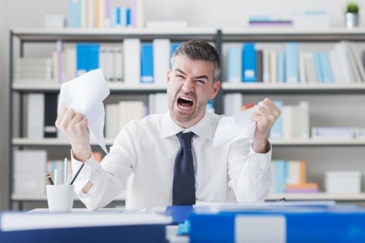 Egy ideges nyakkendős férfi, ordibálva gyűri össze a elmaradt befizetésről szóló felszólítását.