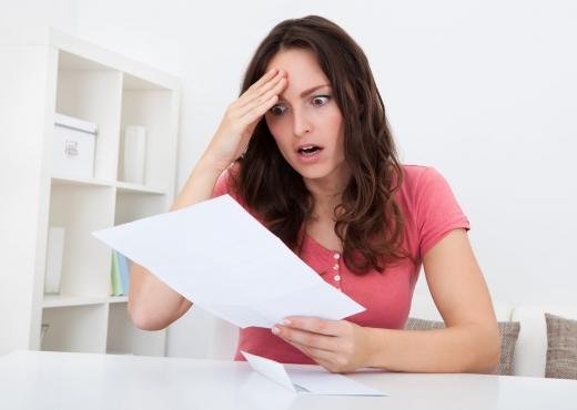 Egy fiatal nő az íróasztalánál, fejét fogva olvassa a fizetési meghagyását.