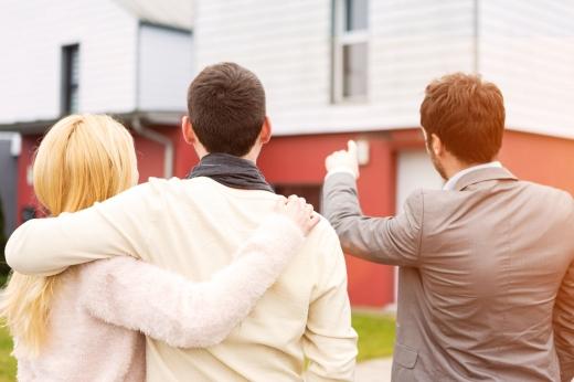 Ingatlanközvetítő egy házat mutat egy fiatal házaspárnak.