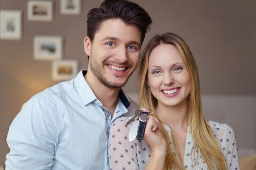 Fiatal pár mosolyogva tartja a kezében az új lakásának a kulcsait.