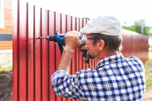 Egy férfi védő szemüvegben fúr egy kerítést.