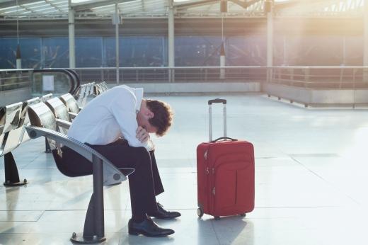 Egy férfi a reptéren ül, előhajolva egy kofferrel.