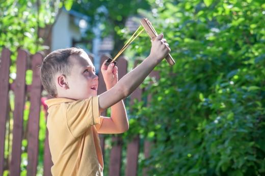 Egy kisfiú a kertbe csúzlival céloz felfelé valamire, amit nem látunk.